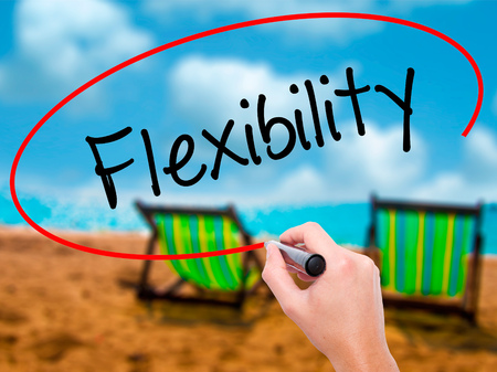 Man Hand writing Flexibility with black marker on visual screen. Isolated on sunbed on the beach. Business, technology, internet concept. Stock Photo