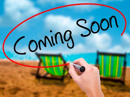 Man Hand writing Coming Soon with black marker on visual screen. Isolated on sunbed on the beach. Business, technology, internet concept. Stock Photo Stock Photo