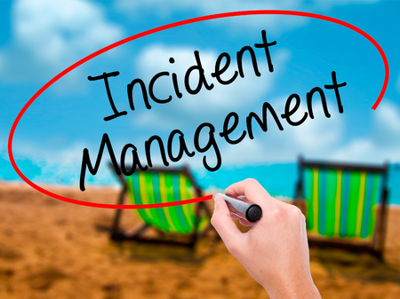 Man Hand writing Incident Management with black marker on visual screen. Isolated on sunbed on the beach. Business, technology, internet concept. Stock Photo