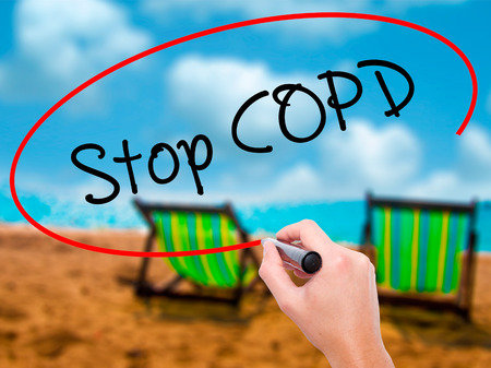 Man Hand writing Stop COPD with black marker on visual screen. Isolated on sunbed on the beach. Business, technology, internet concept. Stock Photo
