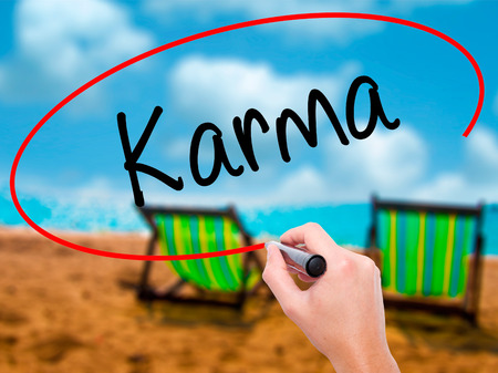 imminent: Man Hand writing Karma  with black marker on visual screen. Isolated on sunbed on the beach. Business, technology, internet concept. Stock Photo Stock Photo