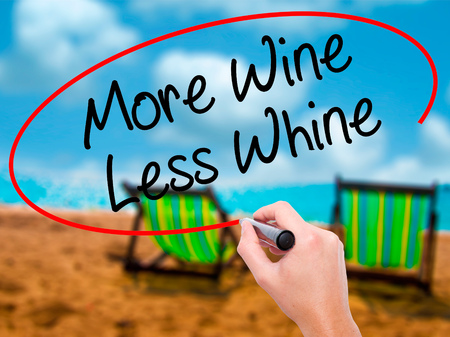 whine: Man Hand writing More Wine Less Whine with black marker on visual screen. Isolated on sunbed on the beach. Business, technology, internet concept. Stock Photo Stock Photo