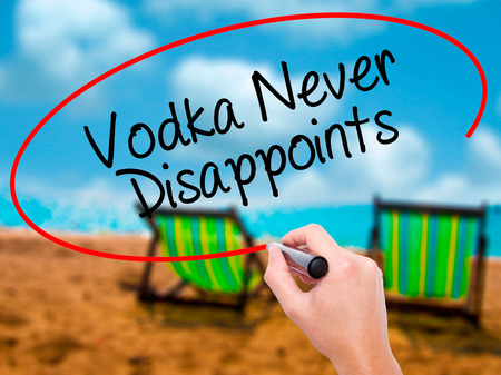 Man Hand writing Vodka Never Disappoints with black marker on visual screen. Isolated on sunbed on the beach. Business, technology, internet concept.