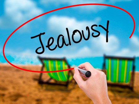 envious: Man Hand writing Jealousy with black marker on visual screen. Isolated on sunbed on the beach. Business, technology, internet concept. Stock Photo