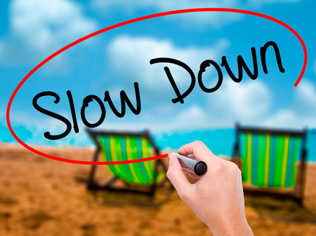 Man Hand writing Slow Down with black marker on visual screen. Isolated on sunbed on the beach. Business,  technology, internet concept. Stock Photo Stock Photo