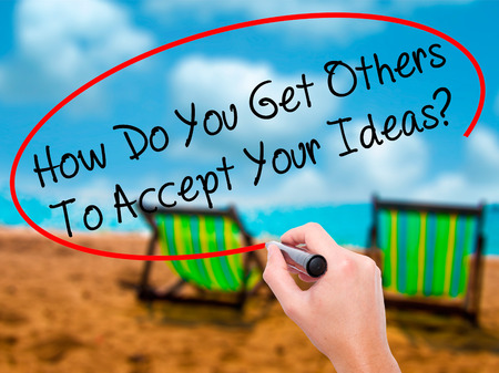 Man Hand writing How Do You Get Others To Accept Your Ideas? with black marker on visual screen. Isolated on sunbed on the beach. Business, technology, internet concept. Stock Photo