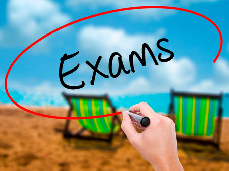 Man Hand writing Exams with black marker on visual screen. Isolated on sunbed on the beach. Business, technology, internet concept. Stock Photo