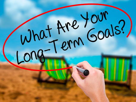 Man Hand writing What Are Your Long-Term Goals? with black marker on visual screen. Isolated on sunbed on the beach. Business, technology, internet concept. Stock Photo