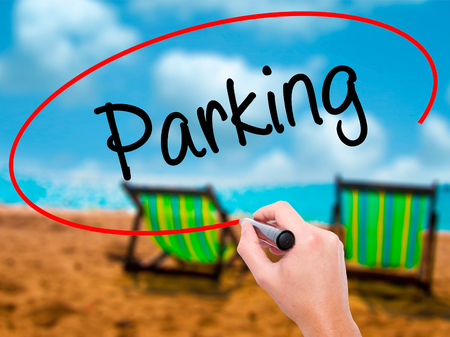 Man Hand writing Parking with black marker on visual screen. Isolated on sunbed on the beach. Business, technology, internet concept. Stock Photo