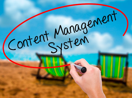 Man Hand writing Content Management System  with black marker on visual screen. Isolated on sunbed on the beach. Business, technology, internet concept. Stock Photo