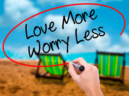 Man Hand writing Love More Worry Less with black marker on visual screen. Isolated on sunbed on the beach. Business, technology, internet concept. Stock Photo Stock Photo