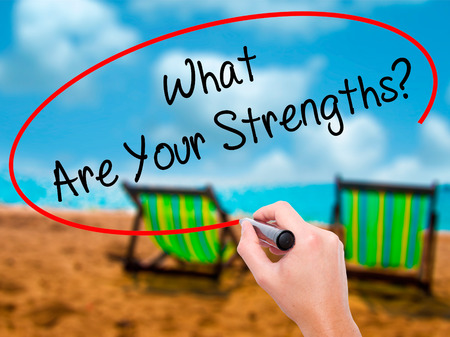 Man Hand writing What Are Your Strengths? with black marker on visual screen. Isolated on sunbed on the beach. Business, technology, internet concept. Stock Photo