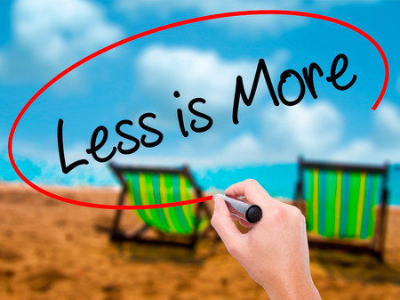 work less: Man Hand writing Less is More with black marker on visual screen. Isolated on sunbed on the beach. Business, technology, internet concept. Stock Photo