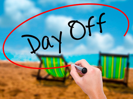 trip hazard sign: Man Hand writing Day Off  with black marker on visual screen. Isolated on sunbed on the beach. Business, technology, internet concept. Stock Photo Stock Photo