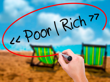 Man Hand writing Poor - Rich with black marker on visual screen. Isolated on sunbed on the beach. Business, technology, internet concept. Stock Photo