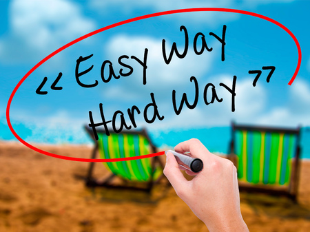 Man Hand writing Easy Way - Hard Way with black marker on visual screen. Isolated on sunbed on the beach. Business, technology, internet concept. Stock Photo Stock Photo