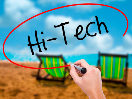 Man Hand writing Hi-Tech with black marker on visual screen. Isolated on sunbed on the beach. Business, technology, internet concept. Stock Photo