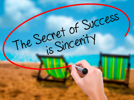 Man Hand writing The Secret of Success is Sincerity with black marker on visual screen. Isolated on sunbed on the beach. Business, technology, internet concept. Stock Photo