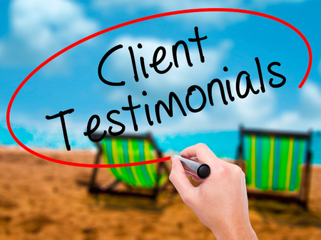 Man Hand writing Client Testimonials with black marker on visual screen. Isolated on sunbed on the beach. Business, technology, internet concept. Stock Photo