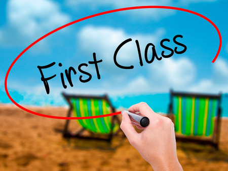 Man Hand writing First Class with black marker on visual screen. Isolated on sunbed on the beach. Business, technology, internet concept. Stock Photo