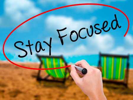 Man Hand writing Stay Focused with black marker on visual screen. Isolated on sunbed on the beach. Business,  technology, internet concept. Stock Photo Stock Photo