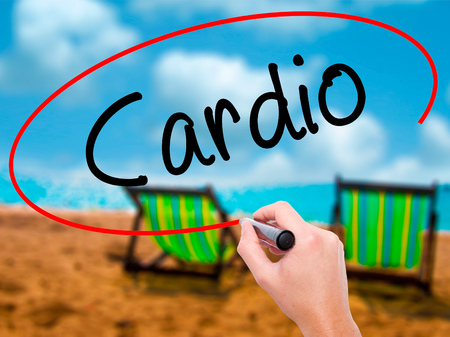 cardiovascular workout: Man Hand writing Cardio with black marker on visual screen. Isolated on sunbed on the beach. Business, technology, internet concept. Stock Photo