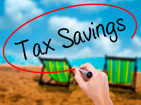 Man Hand writing Tax Savings with black marker on visual screen. Isolated on sunbed on the beach. Business, technology, internet concept. Stock Photo Stock Photo