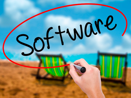 operand: Man Hand writing Software  with black marker on visual screen. Isolated on sunbed on the beach. Business, technology, internet concept. Stock Photo