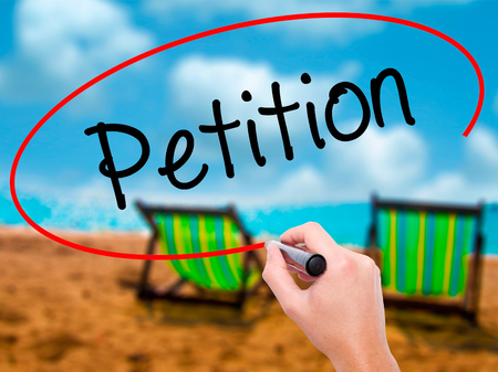 Man Hand writing Petition with black marker on visual screen. Isolated on sunbed on the beach. Business, technology, internet concept. Stock Photo