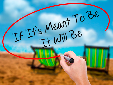 meant to be: Man Hand writing If Its Meant To Be It Will Be with black marker on visual screen. Isolated on sunbed on the beach. Business, technology, internet concept. Stock  Photo