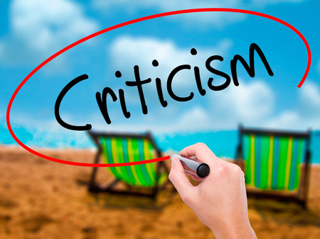 criticism: Man Hand writing Criticism with black marker on visual screen. Isolated on sunbed on the beach. Business, technology, internet concept. Stock Photo Stock Photo