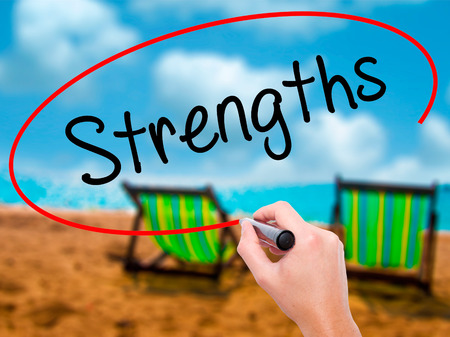 Man Hand writing Strengths with black marker on visual screen. Isolated on sunbed on the beach. Business, technology, internet concept. Stock Photo