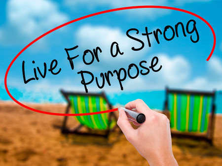 reason: Man Hand writing Live For a Strong Purpose with black marker on visual screen. Isolated on sunbed on the beach. Business, technology, internet concept. Stock Photo