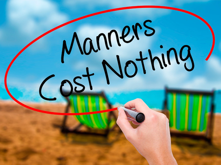 Man Hand writing Manners Cost Nothing with black marker on visual screen. Isolated on sunbed on the beach. Business, technology, internet concept. Stock Photo