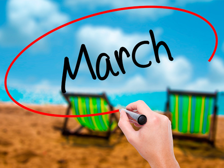 Man Hand writing March with black marker on visual screen. Isolated on sunbed on the beach. Business, technology, internet concept. Stock Photo