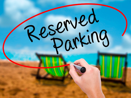 Man Hand writing Reserved Parking with black marker on visual screen. Isolated on sunbed on the beach. Business, technology, internet concept. Stock Photo