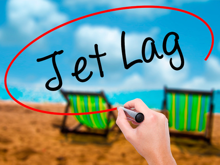 lag: Man Hand writing  Jet Lag with black marker on visual screen. Isolated on sunbed on the beach. Business, technology, internet concept. Stock Photo