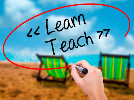 Man Hand writing Learn - Teach with black marker on visual screen. Isolated on sunbed on the beach. Business, technology, internet concept. Stock Photo