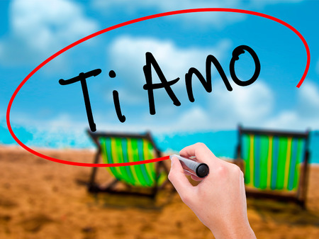 Man Hand writing Ti Amo (I Love You In Italian) with black marker on visual screen. Isolated on sunbed on the beach. Business, technology, internet concept. Stock  Photo