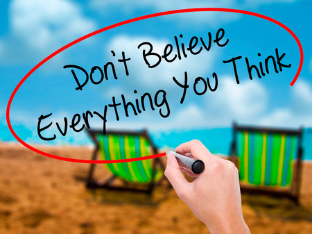 Man Hand writing Dont Believe Everything You Think with black marker on visual screen. Isolated on sunbed on the beach. Business, technology, internet concept. Stock Photo