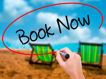 Man Hand writing Book Now with black marker on visual screen. Isolated on sunbed on the beach. Business, technology, internet concept. Stock Photo Stock Photo
