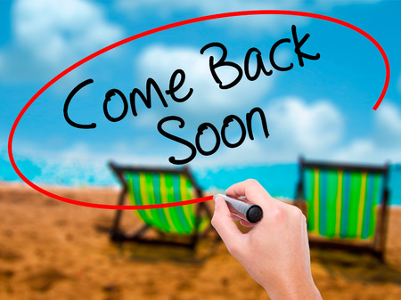 Man Hand writing Come Back Soon with black marker on visual screen. Isolated on sunbed on the beach. Business, technology, internet concept. Stock Photo Stock Photo