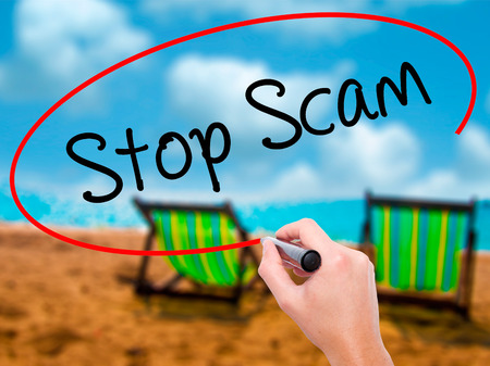 Man Hand writing Stop Scam with black marker on visual screen. Isolated on sunbed on the beach. Business, technology, internet concept. Stock Photo Stock Photo