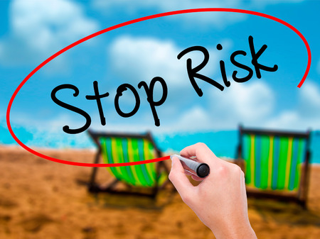 Man Hand writing Stop Risk with black marker on visual screen. Isolated on sunbed on the beach. Business, technology, internet concept. Stock Photo