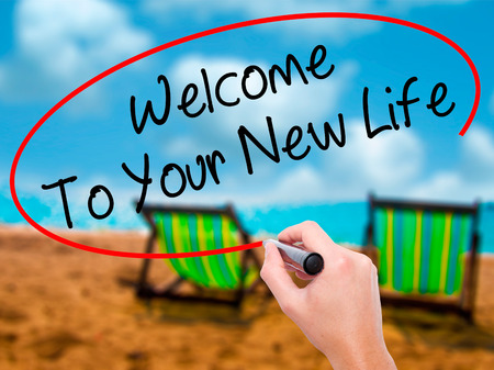Man Hand writing Welcome To Your New Life with black marker on visual screen. Isolated on sunbed on the beach. Business, technology, internet concept. Stock Photo