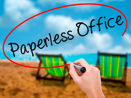 paperless: Man Hand writing Paperless Office  with black marker on visual screen. Isolated on sunbed on the beach. Business, technology, internet concept. Stock Photo