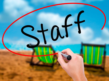 Man Hand writing  Staff with black marker on visual screen. Isolated on sunbed on the beach. Business, technology, internet concept. Stock Photo
