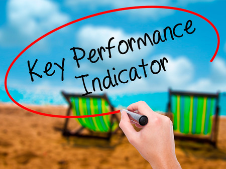 Man Hand writing Key Performance Indicator with black marker on visual screen. Isolated on sunbed on the beach. Business, technology, internet concept. Stock Photo