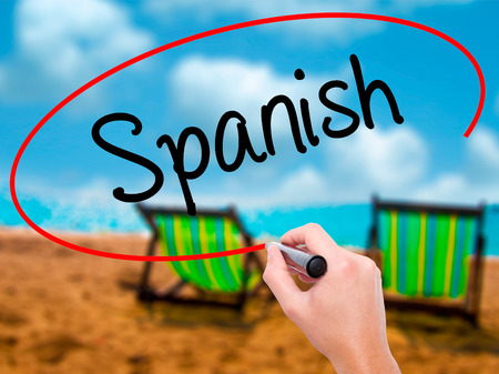 Man Hand writing Spanish with black marker on visual screen. Isolated on sunbed on the beach. Business, technology, internet concept. Stock Photo