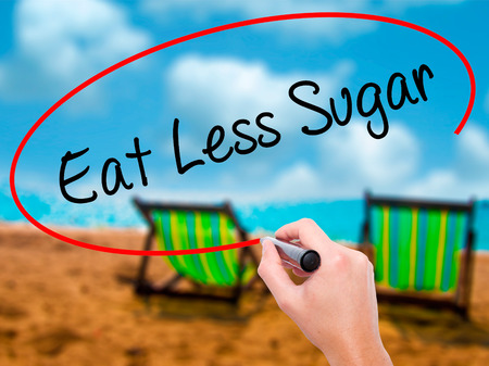 postit note: Man Hand writing Eat Less Sugar  with black marker on visual screen. Isolated on sunbed on the beach. Business, technology, internet concept. Stock Photo